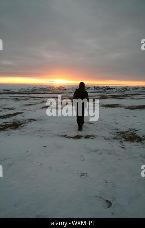 path footprint on white snow men go to sun - Stock Photo