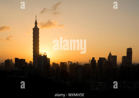 Sunset cityscape with silhouette of 101 skyscraper under dramatic clouds in orange and yellow color in Taipei, Taiwan, Asia. - Stock Photo