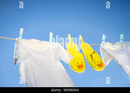 White t-shirts and slippers on the clothesline on a sunny day - Stock Photo