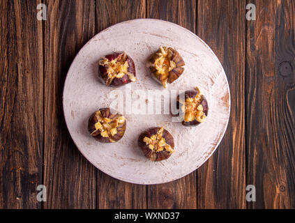 Ripe figs baked with cow's-milk cheese brie and camambert and sprinkled with bread crumbs decorated with mint leaves  on wooden background. Healthy ea - Stock Photo