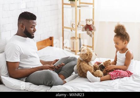 Busy african man browsing on tablet, sad little girl playing with toys alone