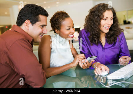 Couple Making Store Purchase Through Computer - Stock Photo