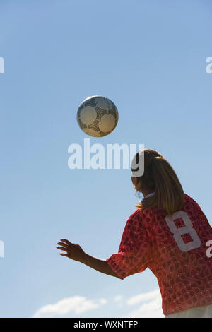 Teenage Girl Heading Soccer Ball - Stock Photo