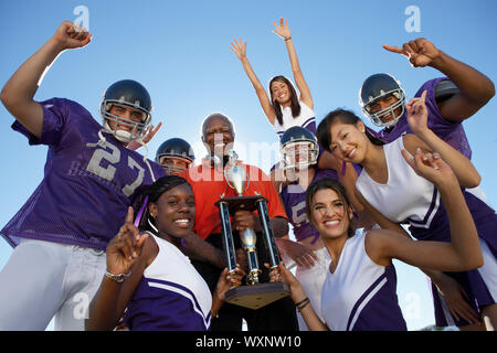 Cheerleaders and Football Players Celebrating with Coach - Stock Photo