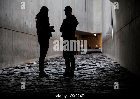 People visiting the Fallen Leaves installation in the Memory Void at the Jewish Museum, Berlin, Germany. - Stock Photo