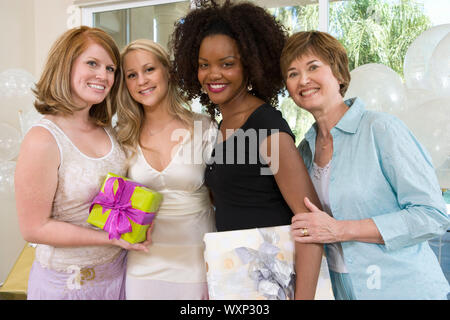 Bride and Friends standing Together holding gifts at Bridal Shower - Stock Photo