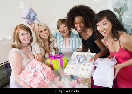 Friends standing Together holding gifts at Bridal Shower - Stock Photo
