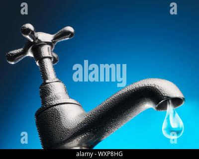 Drop of water trickling from tap close-up (digital composite) - Stock Photo