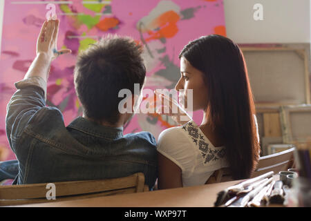 Artists Discussing Painting in Studio - Stock Photo
