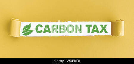torn paper with text CARBON TAX and green leaves in opening - Stock Photo