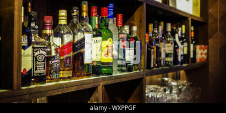 Shanghai, China - Dec 16, 2015: Jack Daniel's, Johnnie Walker, Macallan, Chivas and Jameson whisky bottles on bar counter shelf with dust - Stock Photo