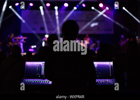 Audio engineer working on a live event - Stock Photo