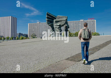 Katowice, Silesia, Poland; September 15, 2019:  A man sightseeing  the Monument of Silesian Insurgents with Superjednostka building in Katowice - Stock Photo