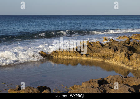 foamy water of blue ocean crashing onto rocky beach lit by golden hour. - Stock Photo