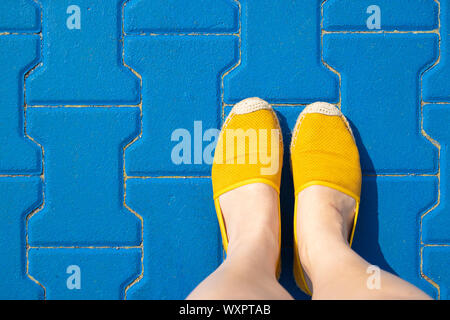 Female legs in yellow shoes or moccasins on a blue tile on a sunny day.