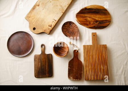 Various wooden tableware. Cutting boards, plate and bowl on linen tablecloth - Stock Photo