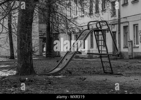 A black and white picture of a slide in the playground of a residential area (Kaunas).