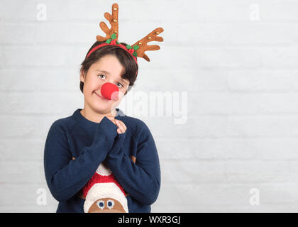 Merry Christmas.Child in a Rudolph Reindeer christmas costume on brick background - Stock Photo