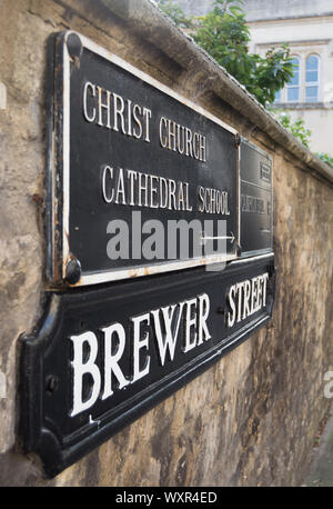 street name sign for brewer street, oxford, england, below a direction sign for christ church cathedral school - Stock Photo