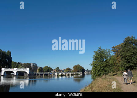 a man and a woman walk on the ham, surrey, england, side of the river thames close to teddington weir - Stock Photo