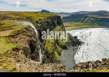 The Allt Mheididh waterfall with spray being blown upwards by the wind, from Rubha Cruinn, Talisker Bay, Minginish, Isle of Skye, Scotland, UK - Stock Photo