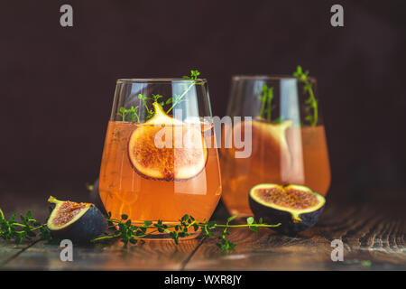Pink cocktail with fig, thyme and ice in glass on dark wooden background, close up. Summer drinks and alcoholic cocktails. Alcoholic or detox cocktail - Stock Photo