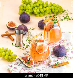 Pink cocktail with fig, thyme, cinnamon and grapes in glass on pink concrete background, close up. Autumn drinks and alcoholic cocktails. Alcoholic co - Stock Photo