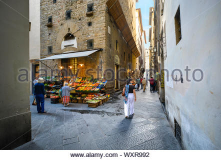 Italians pass by a fresh produce market near a narrow alley away from the main tourist areas in Florence, Italy - Stock Photo