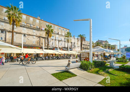 Summer afternoon on the Riva Promenade at the Harbor of Split Croatia as tourists and a bicyclist enjoy the palm trees and sidewalk cafes on the coast - Stock Photo