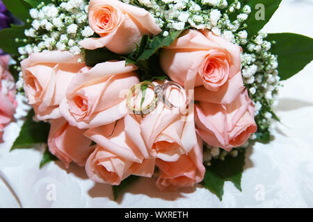 On the photo, there are no people only golden rings and flowers. Background is blurred. Wedding rings on the bride's bouquet from the pink and white - Stock Photo