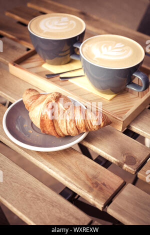 Two large cups of cappuccino and croissant on a table in a street cafe. Vertical shot - Stock Photo