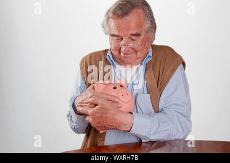 Senior man holding his piggy bank isolated on white - Stock Photo