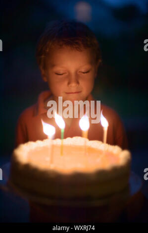 Boy in front of birthday cake - Stock Photo