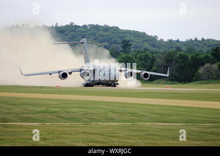 A C-17 Globemaster III with the 437th Airlift Wing at Joint Base Charleston, S.C., takes off June 23, 2016, from Young Air Assault Strip on Fort McCoy's South Post. The C-17 picked up service members with the Joint Communications Unit of Fort Bragg, N.C., who completed a 24-hour training event at Fort McCoy. (U.S. Army Photo by Scott T. Sturkol, Public Affairs Office, Fort McCoy, Wis.) - Stock Photo