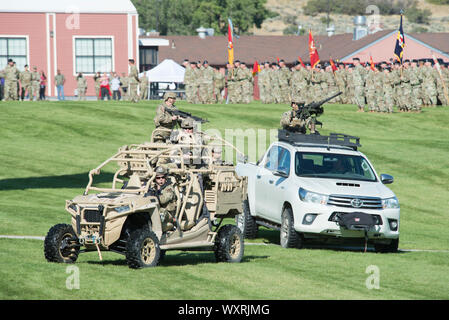 Soldiers assigned to the Utah Army National Guard, storm the parade field in a vehicle demonstration during the annual Governor's Day celebration September 14, 2019, at Camp W. G. Williams, Bluffdale, Utah. Governor's day is deeply rooted in tradition where commanders review the troops in a ceremonial pass-in-review. (U.S. Air National Guard photo by Staff Sgt. Danny Whitlock) - Stock Photo