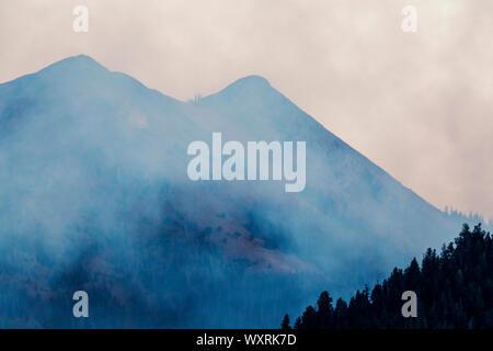 Forest fires in San Luis Valley create smoky skies over Methodist Mountain; Rocky Mountains; near Salida; Colorado; USA - Stock Photo