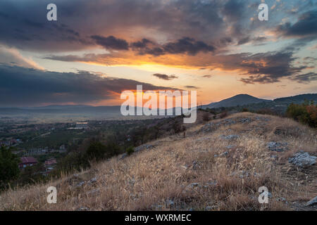 Beautiful view from a hill covered by dry grass and rocks on an epic sunset colors of the sky and distant hospital and village - Stock Photo
