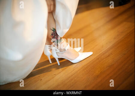 Rose tattoo and white pointed high heels. - Stock Photo