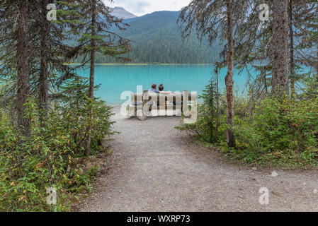 Yoho National Park, British Columbia, Canada - September 08, 2019:  two people sit on a park bench facing Emerald Lake - Stock Photo