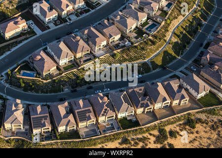 Aerial late afternoon view of suburban residential rooftops in the San Fernando Valley area of Los Angeles, California. - Stock Photo