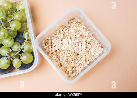 the right breakfast of green and black grapes and cereal muesli. granola and fresh fruits in a lunchbox on a pastel beige background - Stock Photo