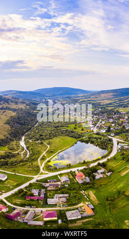 Vertical landscape of settlement in valley between mountains. Sunset time, end of summer. Aerial drone view of urban village Pidbuzh in Carpathians - Stock Photo