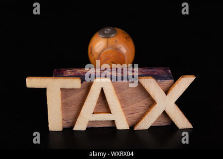 Inscription tax old rubber stamp. Office accessories on a dark table. Black background. - Stock Photo
