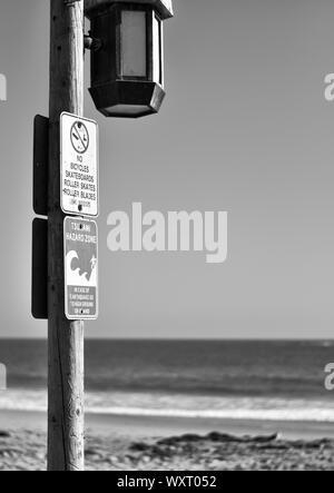 Tsunami hazard zone sign on Laguna Beach in Los Angeles, black and white image - Stock Photo