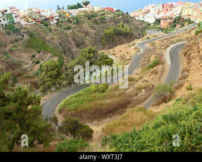 Extreme narrow winding route along a Barranco above the city of Los Realejos in the north of the Canary Island of Tenerife overlooking the colorful ho - Stock Photo
