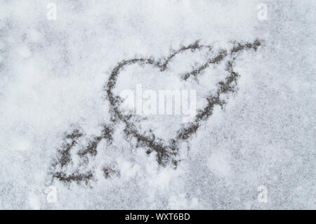 Heart pierced by an arrow, a sign of separation painted on the snow, soft blue background color - Stock Photo