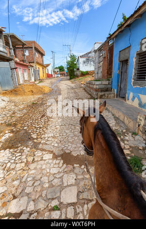 Riding on top of a Horse in the streets of a small Cuban Town during a vibrant sunny day. Taken in Trinidad, Cuba. - Stock Photo