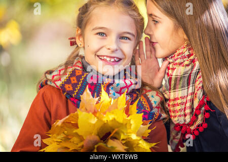 Two cute smiling 8 years old girls chatting in a park on a sunny autumn day. - Stock Photo