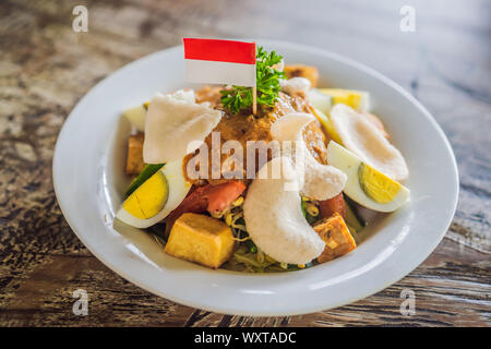 Gado-gado Indonesian salad served with peanut sauce. Ingredients: tofu, spinach, string beans, soy sprouts, potatoes, cucumber and boiled eggs - Stock Photo
