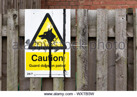 Close up of Caution Guard dogs on patrol 24/7 sign at Market Harborough in Leicestershire, England, UK - Stock Photo